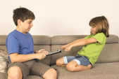 Kids arguing for playing with a digital tablet on a sofa. — Stockfoto