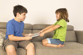Kids arguing for playing with a digital tablet on a sofa. — Stock Photo