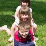 Three lively children on grass — Stock Photo