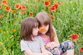 Two small children with flowers — Stock Photo