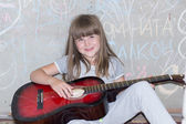 Cheerful girl 6-7 years, playing guitar — Stock Photo