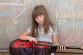 Girl 6-7 years old, sitting with a guitar — Stock Photo