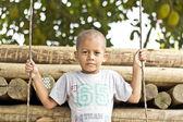 Boy standing over swing — Stock Photo
