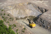 Yellow excavator stonecutter in a quarry for granite — Stock Photo
