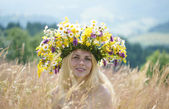 Girl in big wreath on a meadow — Stock Photo