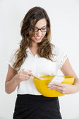 Young business woman with a Smartphone and a bowl in her hand — Stock Photo