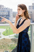 Young woman having a phone call on the porch — Stockfoto