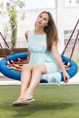 Beautiful girl on a swing on the park — Stockfoto