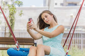 Beautiful girl texting and taking self picture on the park — Stock Photo