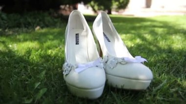 White wedding bridal shoes on grass — Stockvideo