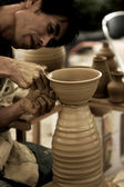 A potter creating an earthen jar on the circle — Stock Photo