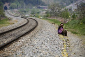 Elderly man sits along the railroad tracks — Stock Photo