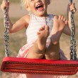 Cute little girl laughs while swinging — Stock Photo #46231491