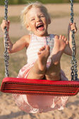 Cute little girl laughs while swinging — Stock Photo