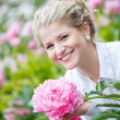 Beautiful happy woman in flower garden smiling — Stock Photo #50335097