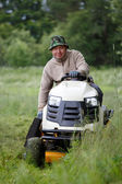 Man with lawn mower — Stockfoto