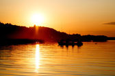 Silhouette of fishing people in boat in sunset time — Stock Photo
