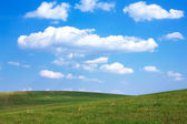 Rolling green hills and blue sky with white clouds — Stock Photo