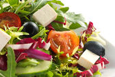 Detail shot of greek salad on a whte plate — Stock Photo