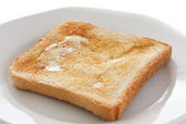 Slice of white buttered toast on a plate — Stock Photo