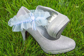 Light blue lace garter with silver high heel shoes — Stock Photo