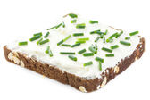 Cut fresh chives on thickly spread cream cheese on dark health bread. — Stock Photo