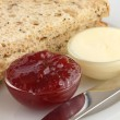 Two slices of multigrain bread with jam and butter in dishes — Stock Photo #49397831