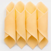 Cheelse slices neatly rolled up on a white surface. — Stock Photo