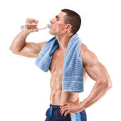 Young muscular man with blue towel over neck, drinking water, isolated on white background — Stock Photo