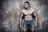 Bell'uomo muscoloso sexy sullo sfondo della parete — Foto Stock