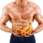 geformt und gesunden Körper Mann hält ein frisches Obst, geformte Bauch-, isoliert auf weißem Hintergrund — Stockfoto #47722051
