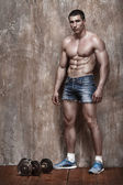 Handsome muscle man on wall background — Stock Photo