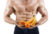 Shaped and healthy body man holding a fresh fruits, shaped abdominal — Stock Photo