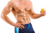 Healthy muscular man holding a glass with juice, shaped abdominal — Stock Photo