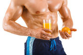 Healthy muscular man holding a glass with juice and orange, shaped abdominal — Stock Photo