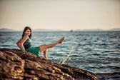 Girl sitting on the rocks on the shore of the Adriatic Sea in the green dress — Stock Photo