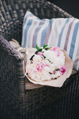 Peonies in a paper bag lying on a wicker chair — Stock Photo