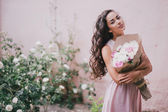 Beautiful girl with a bouquet of peonies — Stock Photo