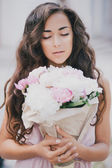 Beautiful girl with a bouquet of peonies — Stockfoto
