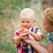 Fashion baby boy and his mother smelling flower — Stock Photo #47457315