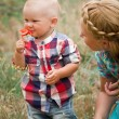Fashion baby boy and his mother smelling flower — Stock Photo #47457335