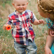 Fashion baby boy and his mother smelling flower — Stock Photo #47457359