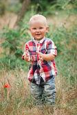 Fashion baby boy walking in grass — Stock Photo