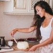 Young beautiful woman making cake at the kitchen — Stock Photo