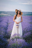 Beautiful young woman posing in a lavender field — Foto de Stock