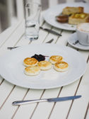Breakfast with cheesecakes, toast, cappuccino and macarons — Stock Photo