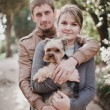 Young attractive couple going for a walk with their dog — Stock Photo #49622357