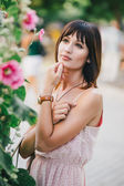 Beatiful woman in a pink dress posing near pink flowers — Stock Photo
