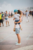 Young mother and her son walking in city streets — Stock Photo