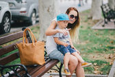 Fashion mother and son walking in a park — Stock Photo
